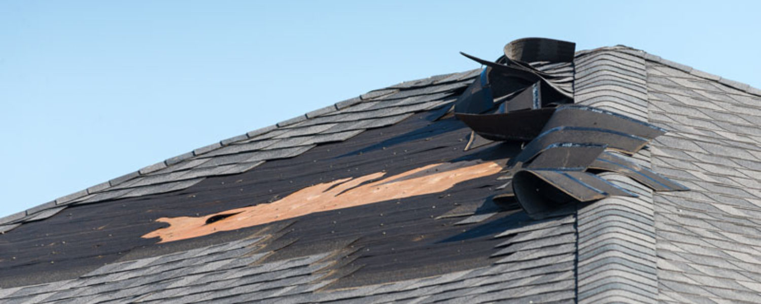 Roof with missing shingles and storm damage