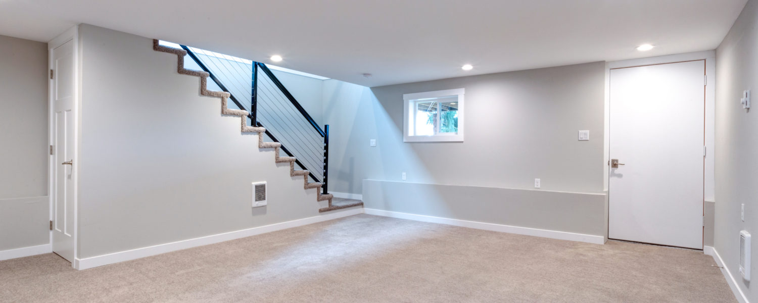 Finished basement with grey walls, beige carpet, and white trim